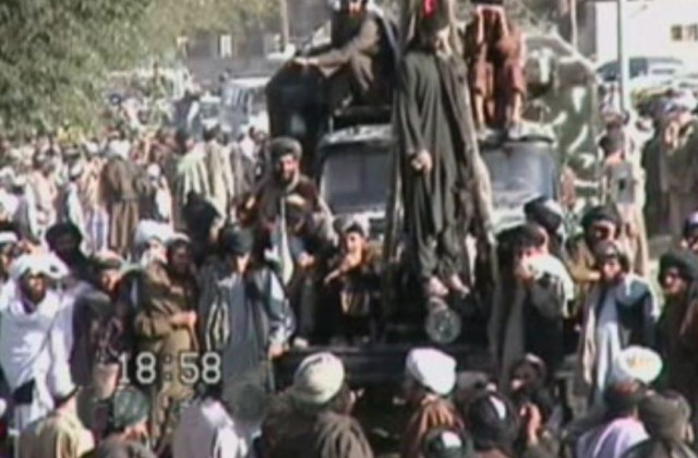 Taliban forces hang a man from a crane in a twisted display to the public