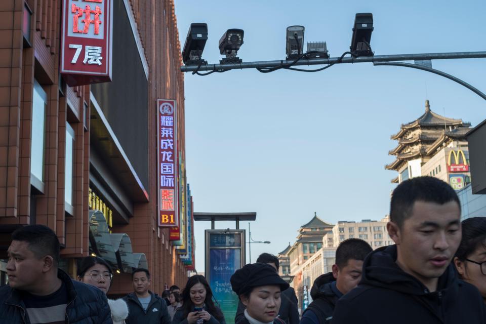 Pedestrians walk below CCTV cameras in Wangfujing Street in Beijing, China