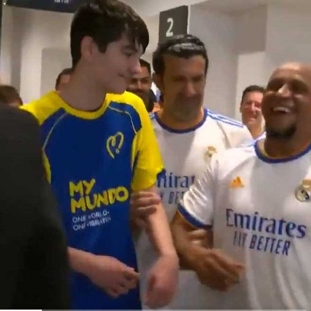 Roberto Carlos quickly gets the joke after Luis Figo made his 5ft 6ins Real Madrid team-mate stand next to a lanky mascot