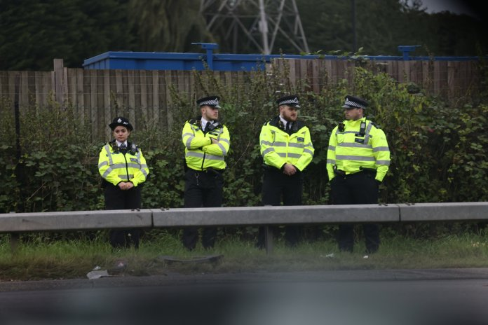 Police in numbers keep an eye on Insulate Britain's protesters as they march on M25 .  try to block