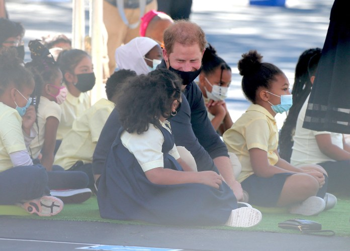 The Duke seen laughing with a little girl during Meghan's reading