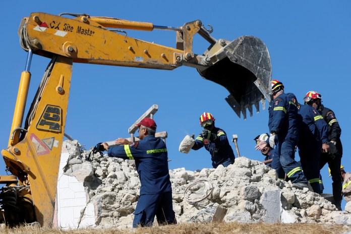 Emergency personnel remove debris