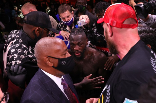 Tyson Fury pictured trying to embrace Deontay Wilder