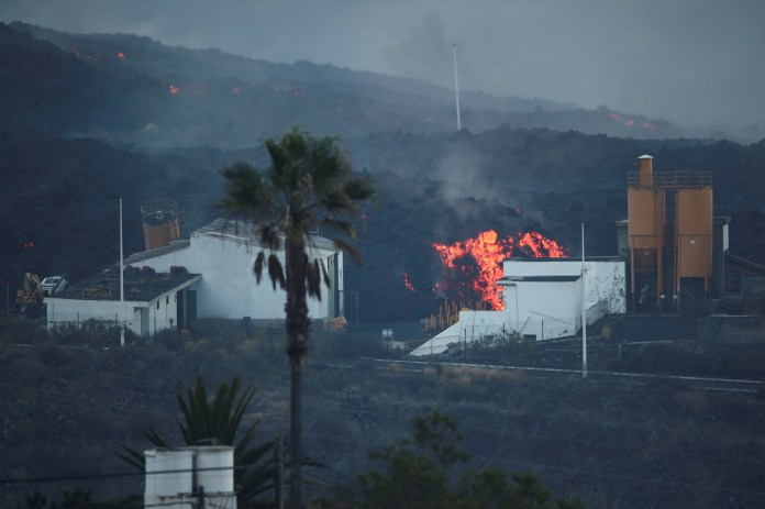 Lava rolls down behind a cement factory in Los Llanos