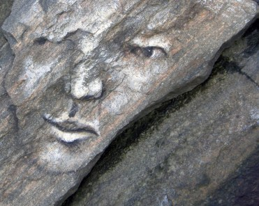 Painted stone face - squinting with one eye