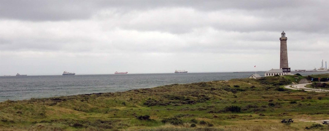 Tramp ships at anchor and the Grey lighthouse looking south from Grenen