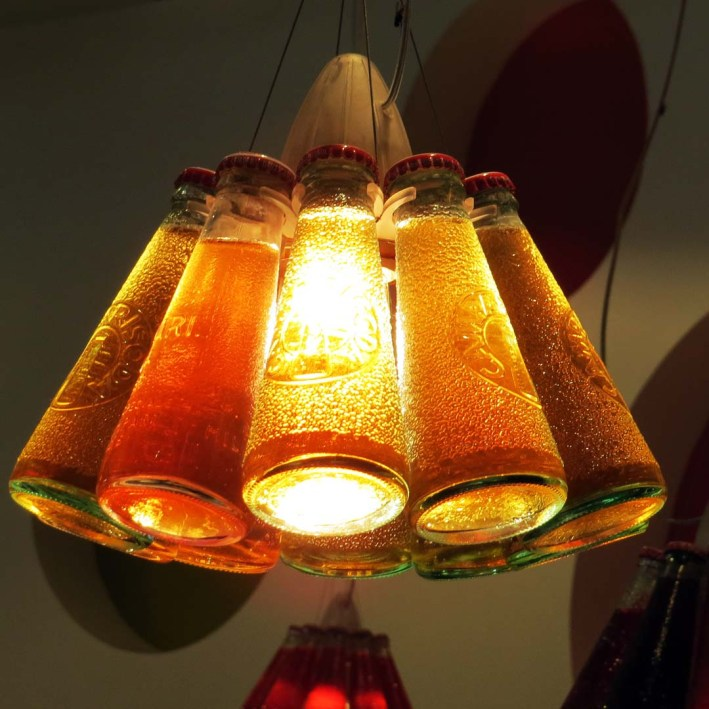 Lamps in the café shaded by bottles of soda