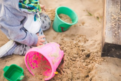 Image of a child learning by playing in sand. Preschool learning happens in a natural, playful context.