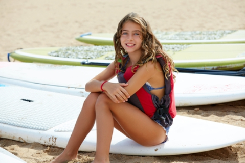 young girl sitting on the beach with stand up paddle boards