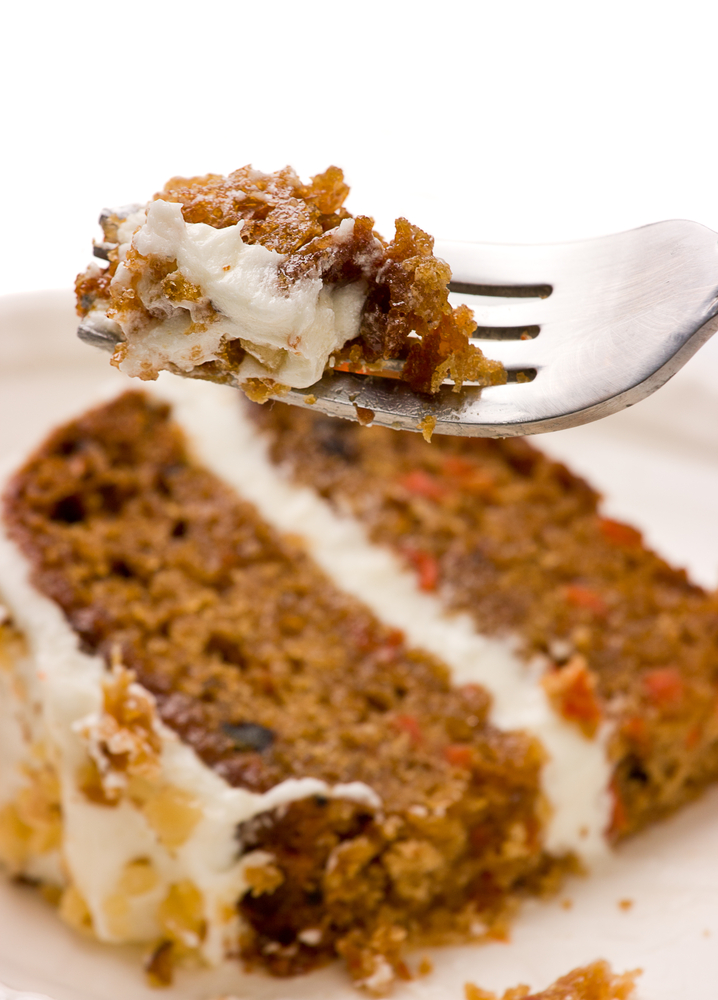 slice of paleo carrot cake with forkful of frosted cake