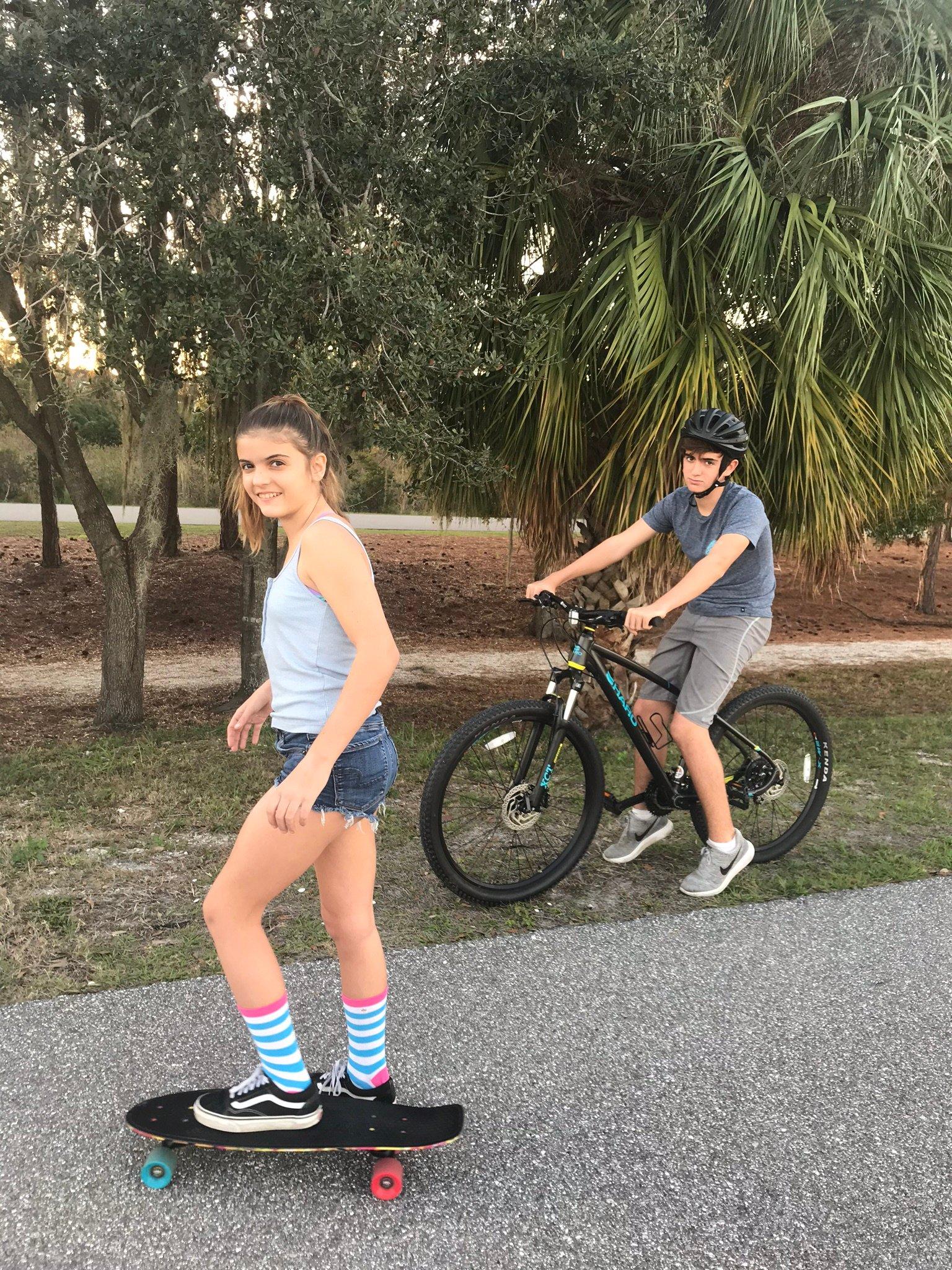 Teen skateboarding and biking