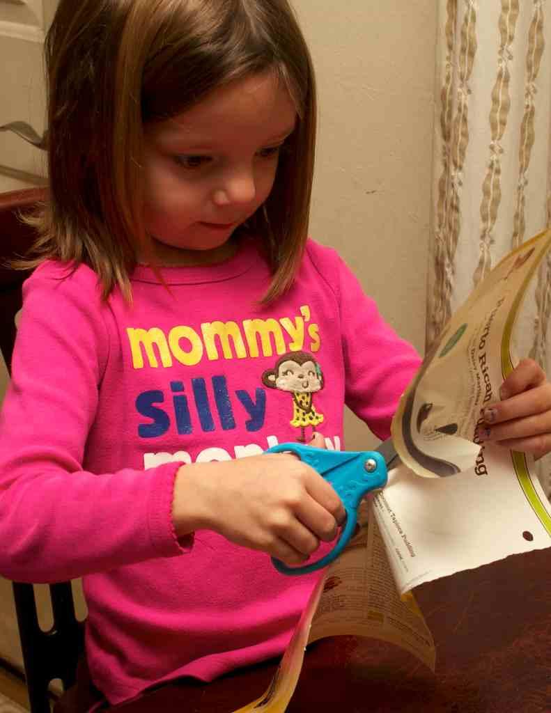 Preschooler cutting from a magazine
