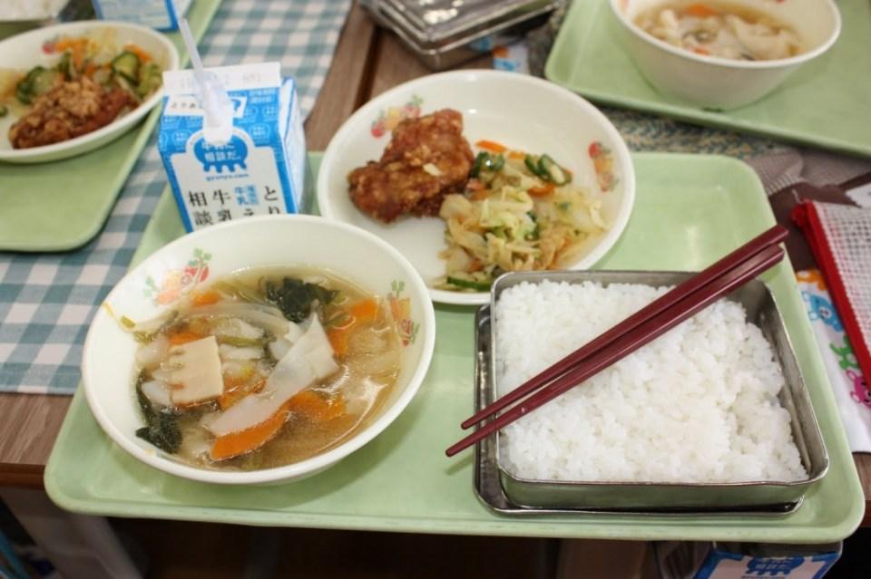 Voorbeeld van een schoollunch. De gerechten wisselen van traditioneel Japans tot Westers of een combinatie daarvan. Maar een pakje melk zit er áltijd bij.