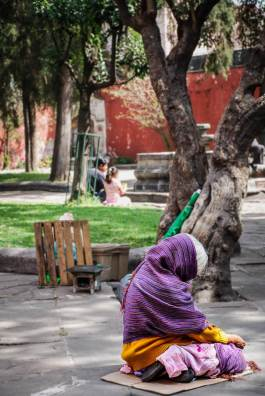 Homeless lady sitting in a park in Mexico