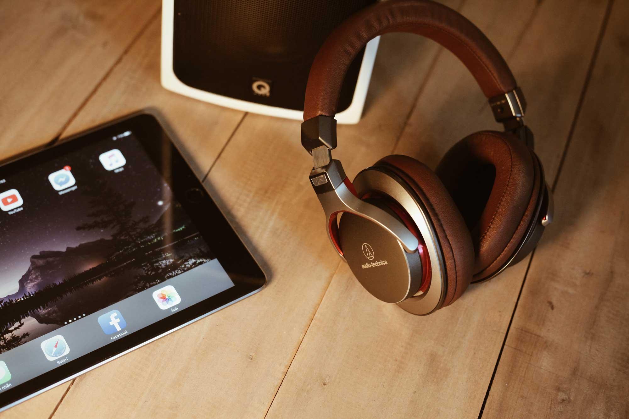 headphones, speaker and ipad on timber desk