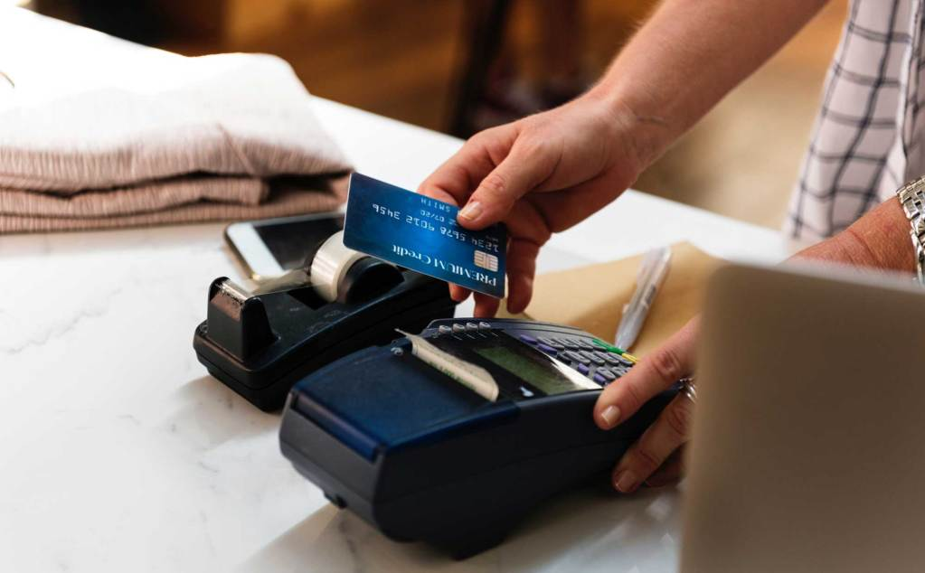 man using credit card machine to purchase a jumper