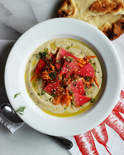 israeli style hummus with pickled shredded carrots, watermelon radishes and dill