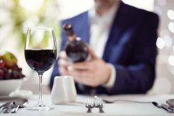 businessman-reading-a-wine-bottle-label-in-restaurant-picture-id924365074