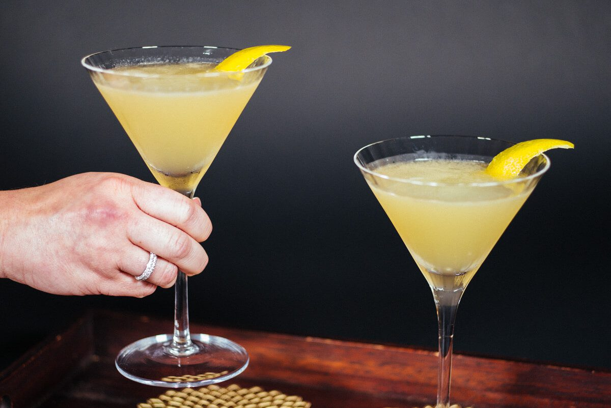 serving sidecars cocktails from a tray with a twist of lemon