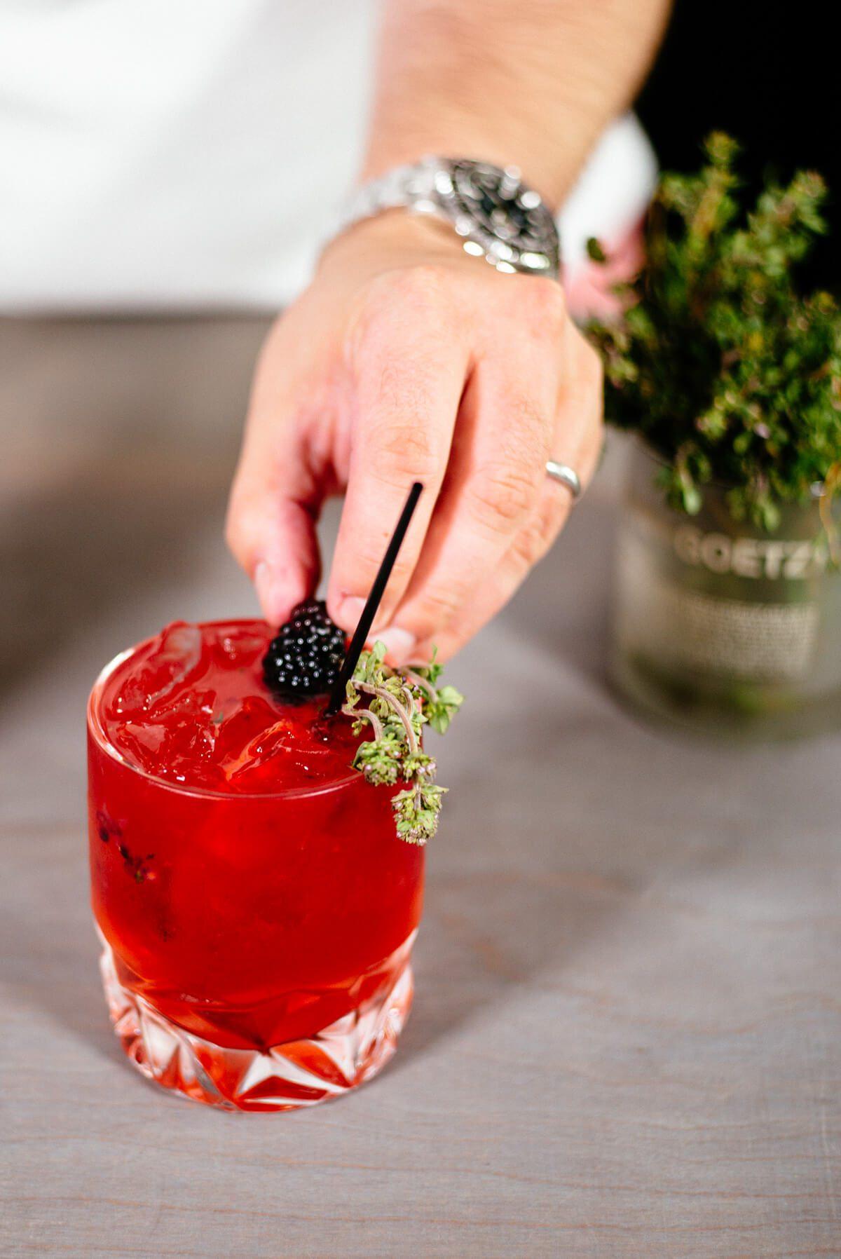 Garnishing the blackberry elderflower gin and tonic.
