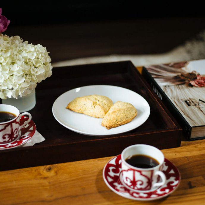Eating lemon poppy scones for breakfast with coffee.