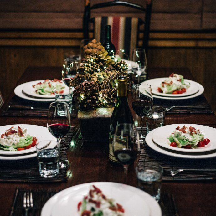 The table was set with wine, pinecones, and lights for a steakhouse style steak dinner with the taste sf in tahoe