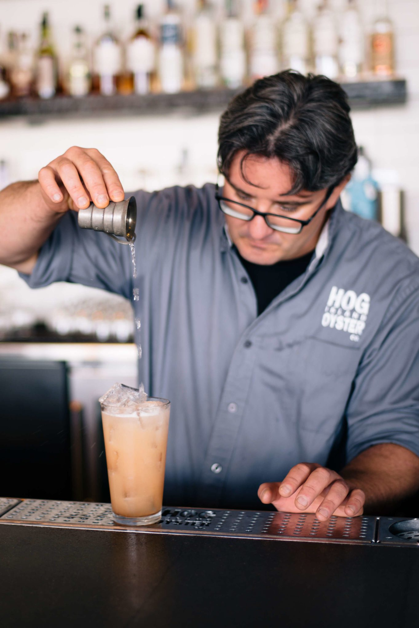Saul Ranella of Hog Island Oyster Company in San Francisco double straining the punch drunk bitter cocktail with St George Gin and soda water, The Taste SF