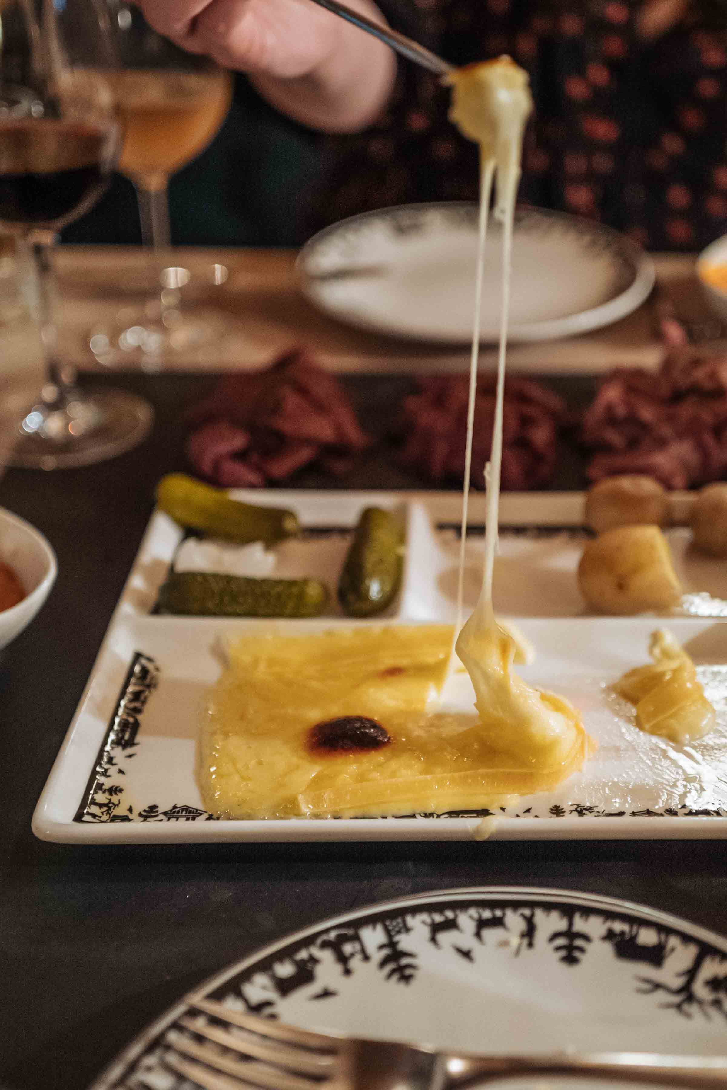 Stretch that cheese! Here's where to go for the best raclette dinner in Klosters. Use our guide to know where to go and the best restaurants to find that and fondue with our guide to Klosters. | thetastesf.com #travel #switzerland #winter #food #cheese