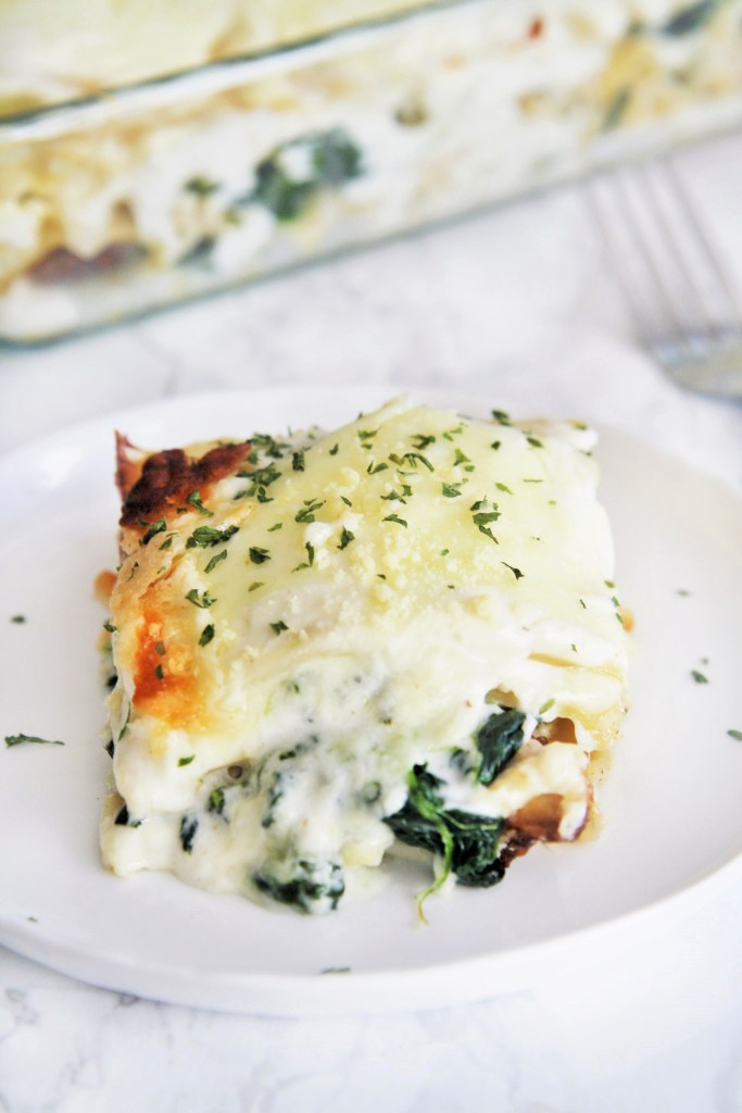 Cheesy, satisfying lasagna casserole made with chicken and spinach layered between lasagna noodles and creamy white sauce.
