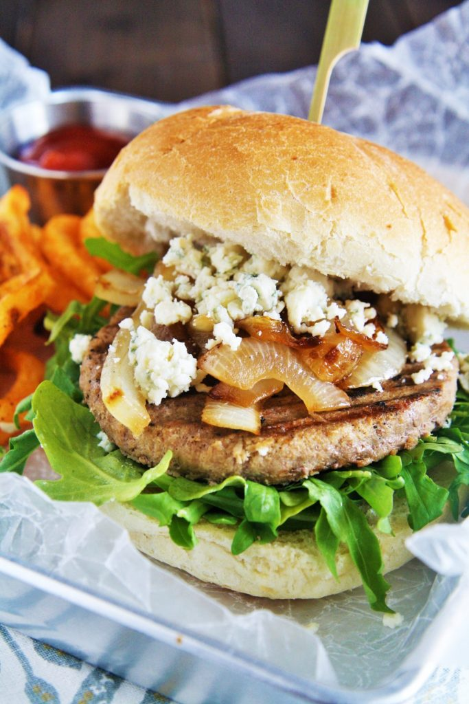 Serve up these savory turkey burgers topped with caramelized onions, blue cheese, and garlic aioli on your next grill night!
