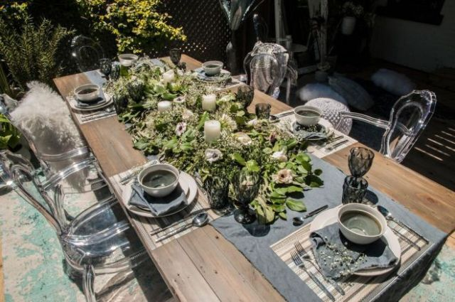 Green and white floral centrepiece on urban barn table