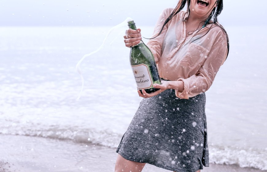 girl on beach with bottle of champagne