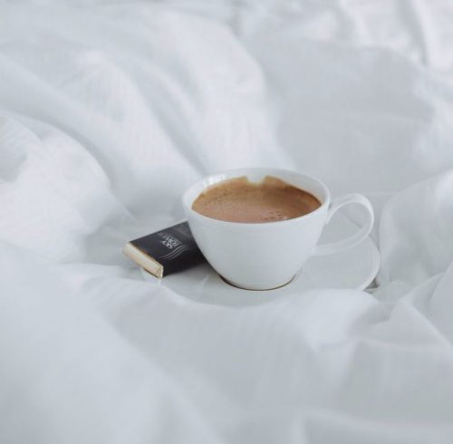 coffee on bed with white sheets