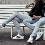 couple on bench wearing addidas shoes