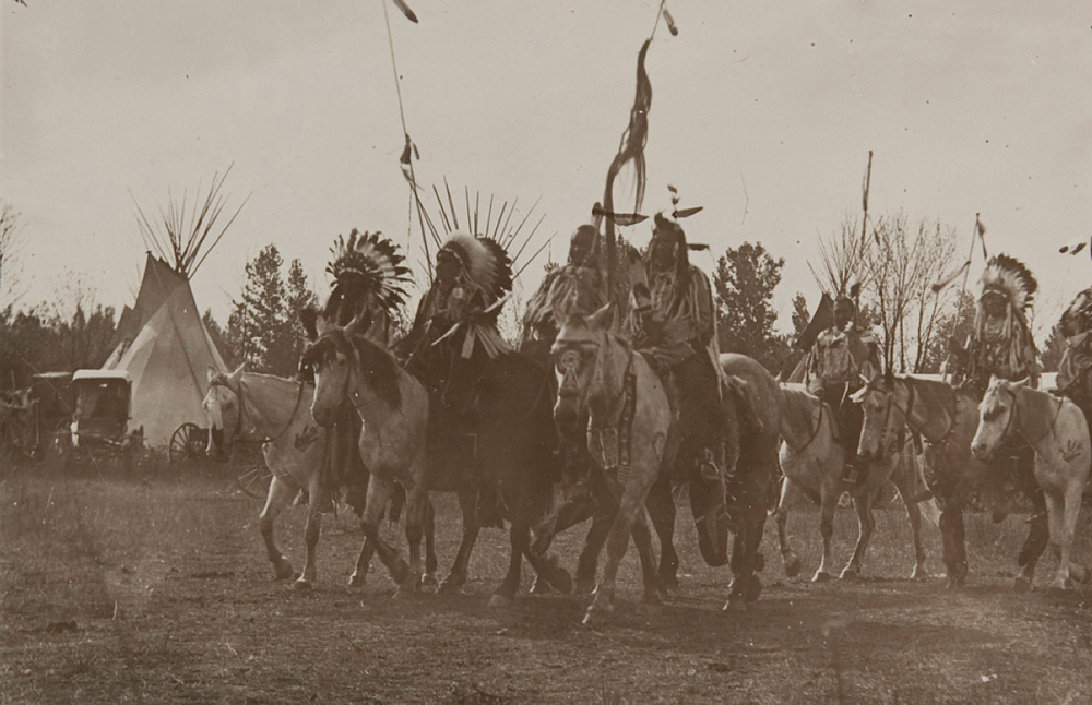 Untitled (Native Americans wearing headdresses on horseback), c. 1910 Photographed by Richard Throssel (Cree, adopted Crow; 1882-1933). Gelatin silver print on paper. Museum of Photographic Arts.