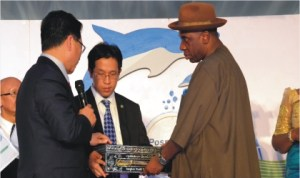 Rivers State Governor, Rt Hon Chibuike Amaechi (right), receiving Port Harcourt World Book Capital 2014 from Deputy Governor, Bangkok, Mr K  Amond (left), during the celebration of the Port Harcourt World Book Capital, at Hotel Presidential, Port Harcourt, Wednesday. With them is A representative of Bangkok