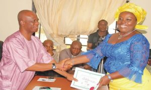 The Resident Electoral Commissioner for Bayelsa State, Mr Baritor Kpagih (left), presenting certificate-of-return to Princess Ingo Iwari (pdp), member-elect representing Ogbia Constuency 2 in Bayelsa House of Assembly, at the inec office in Yenagoa last Tuesday. Photo: NAN