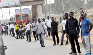Stranded commuters at Lugbe Bus Stop as a result of fuel scarcity in Abuja on Friday last week.