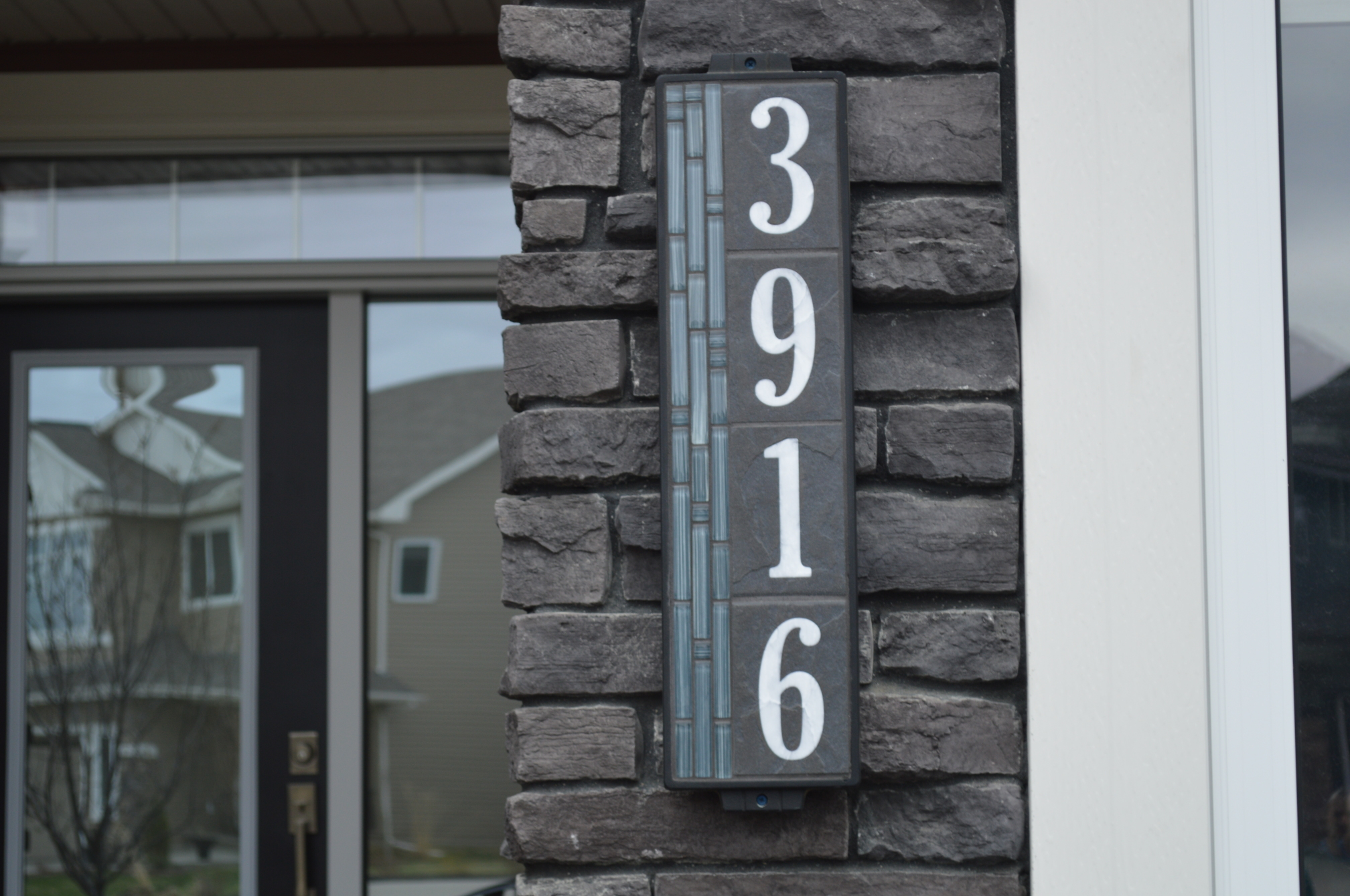 "6""x24"" Blue Bamboo House Number Sign Installed on a Home"