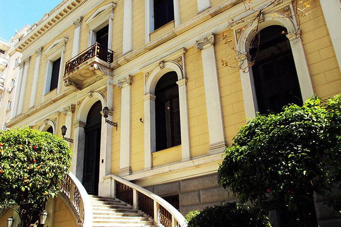 ΙΛΙΟΥ ΜΕΛΑΘΡΟΝΕμβληματικό κτίριο πρώην κατοικίας, που σχεδιάστηκε το 1879 από τον αρχιτέκτονα Ε.Τσίλερ και σήμερα στεγάζει το Νομισματικό Μουσείο. Η αποκατάσταση του έγινε από τις αρχιτέκτονες Έ. Μισαηλίδου-Φιλιπποπούλου και Μ. Χρυσουλάκη το 1984 και από την Ε. Ανδρούτσου στις αρχές του 21ου αίωνα.