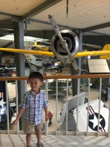 Tyler with a vintage airplane at the Naval Aviation Museum