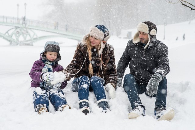 Family hanging out having fun in the snow during winter