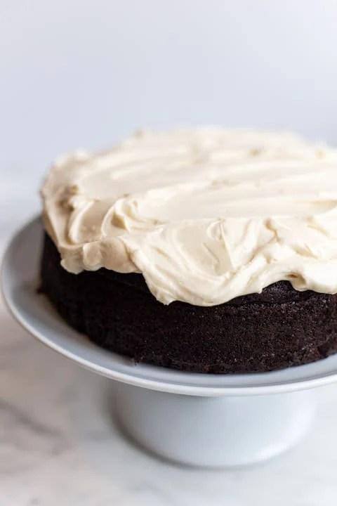 guinness beer chocolate cake with cream cheese frosting on a white cake stand