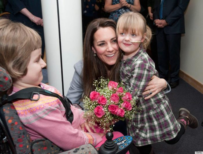 Kate Middleton is hugged by Demi-Leigh Armstrong, 5, as she visits the Shooting Star House Children's Hospice on October 18, 2013.
