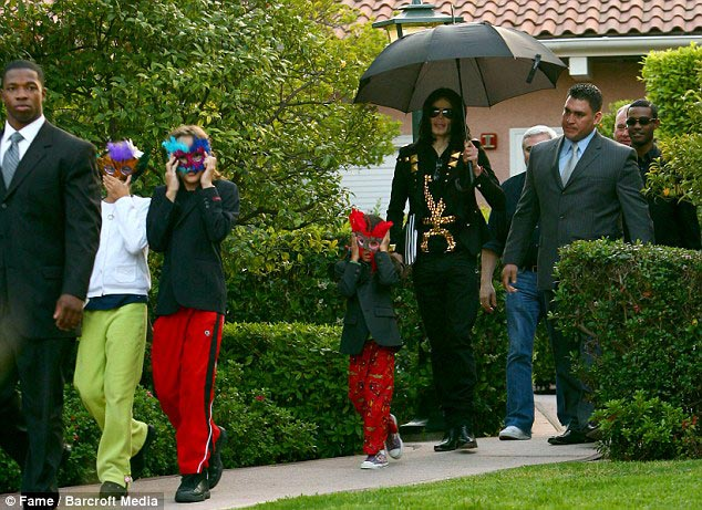 Michael Jackson (Under Umbrella) with children in front. While the legendary singer was a live his children lives under a veil of secrecy