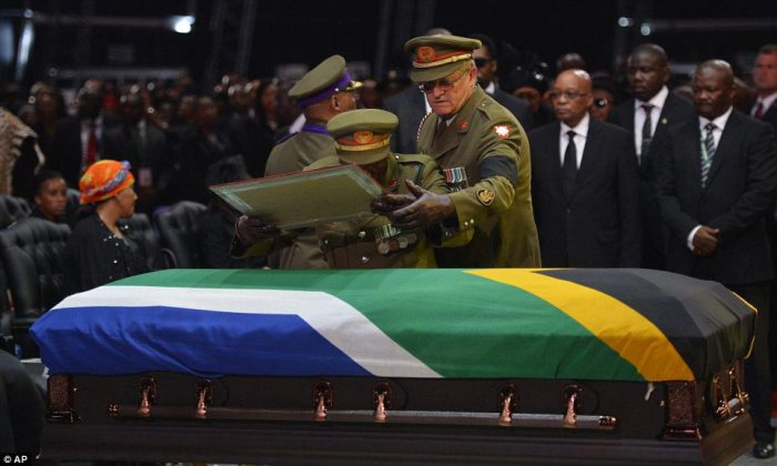 Tribute: A military officer places the framed flag of South Africa on top of Mandela's coffin