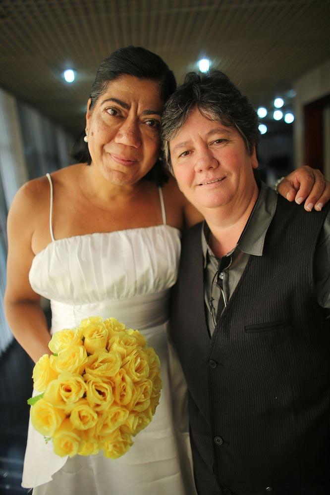 Newly married couple Ana Cristina Ribero Martins (R) and Claudia Almeida Martins, together 23 years, pose at what was billed as the world's largest communal gay wedding on December 8, 2013 in Rio de Janeiro, Brazil. 130 couples were married at the event which was held at the Court of Justice in downtown Rio. In May, Brazil became the third country in Latin America to effectively approve same-sex marriage via a court ruling, but a final law has yet to be passed. (Photo by Mario Tama/Getty Images)