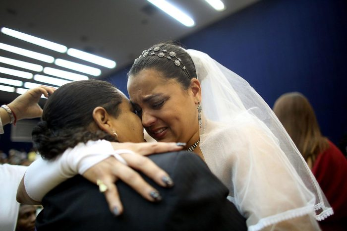 Newly married couple Ana Paula and Juliana (L) react at what was billed as the world's largest communal gay wedding on December 8, 2013 in Rio de Janeiro, Brazil. 130 couples were married at the event which was held at the Court of Justice in downtown Rio. In May, Brazil became the third country in Latin America to effectively approve same-sex marriage via a court ruling, but a final law has yet to be passed. (Photo by Mario Tama/Getty Images)