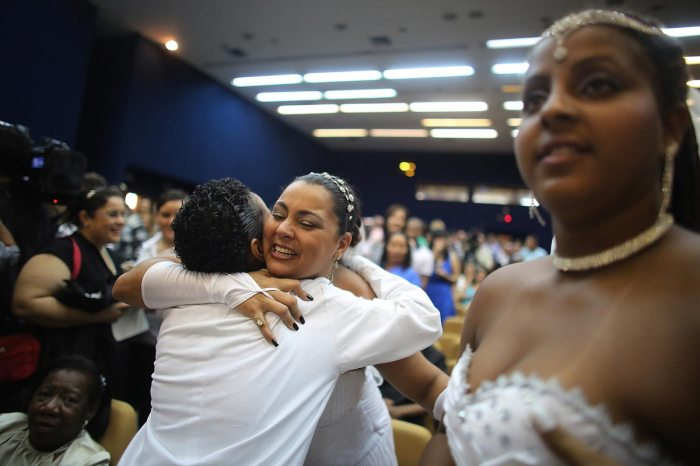 Newly married woman Ana Paula (LEFT C) is hugged at what was billed as the world's largest communal gay wedding on December 8, 2013 in Rio de Janeiro, Brazil. 130 couples were married at the event which was held at the Court of Justice in downtown Rio. In May, Brazil became the third country in Latin America to effectively approve same-sex marriage via a court ruling, but a final law has yet to be passed. (Photo by Mario Tama/Getty Images)