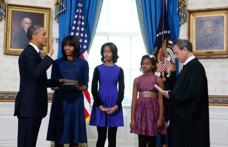 US President Barack Obama (L) takes the oath of office from US Supreme Court Chief Justice John Roberts as first lady Michelle Obama holds the bible and their daughters Malia (C) and Sasha (2nd R) look on in the Blue Room of the White House in Washington on January 20, 2013. AFP PHOTO/Larry Downing/PoolLARRY DOWNING/AFP/Getty Images ORG XMIT: -